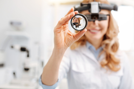 Skillful careful ophthalmologist making observations