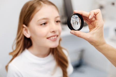 optician: Careful intelligent girl following doctors instructions