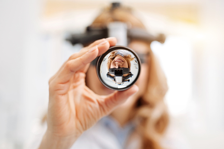 Focused scrupulous ophthalmologist doing a professional checkup Stock Photo