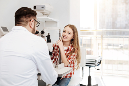 Bright positive patient sitting at ophthalmologists office