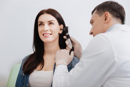 Attentive doctor doing ear exam of pretty woman Foto de archivo
