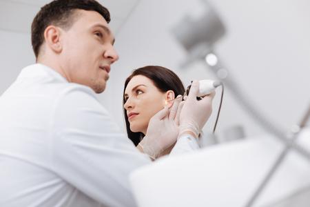 Laag hoekbeeld van professionele arts die vrouwelijk oor controleert Stockfoto