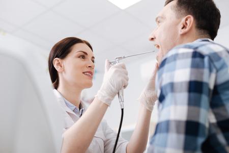 Attractive otolaryngologist doing throat exam of male patient Stock Photo