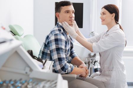 Delighted female otolaryngologist sitting opposite her patient