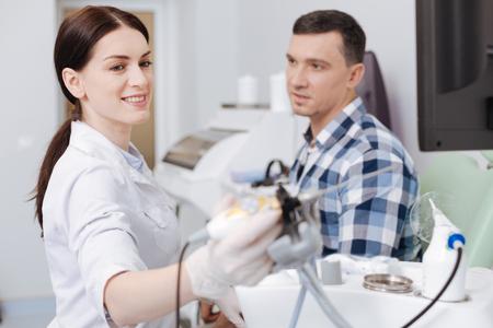 Positive delighted otolaryngologist taking instrument