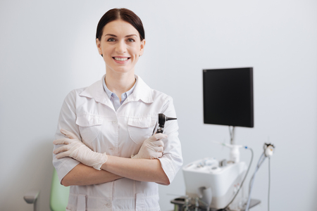 Positive delighted female otolaryngologist posing on camera Stock Photo