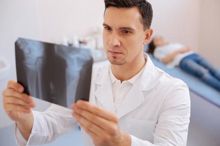 luxacion: Doctor serio inteligente mirando la foto de rayos X