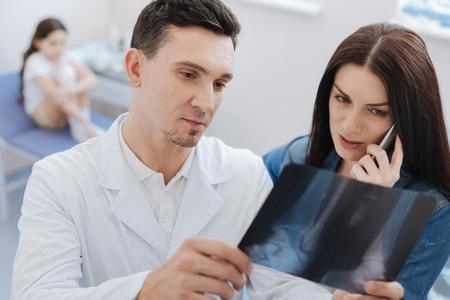 luxacion: Agradable mujer ansiosa de pie cerca del médico