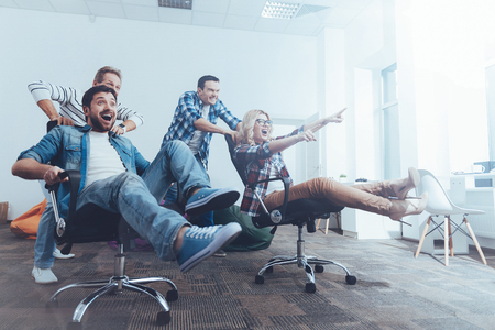 Positive colleagues having fun with office chairs Stock Photo