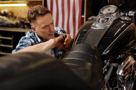 Precise good mechanic fixing the bolt