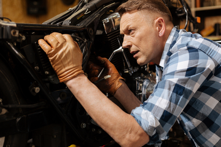 old school bike: Skilled local professional fixing the engine Stock Photo
