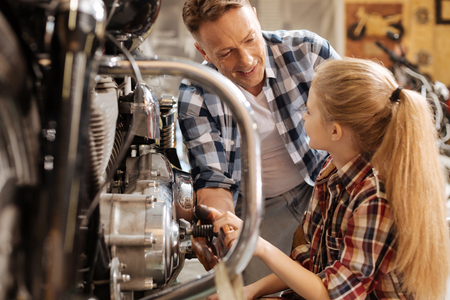 Capable mechanic telling daughter about mechanisms of the bike