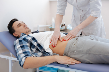 Handsome nice man being examined by the doctor