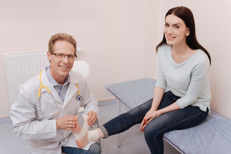 Friendly professional rheumatologist happy assisting his patient Stock Photo