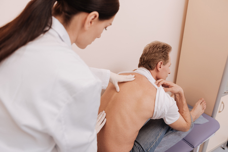 Obedient middle aged patient leaning forward