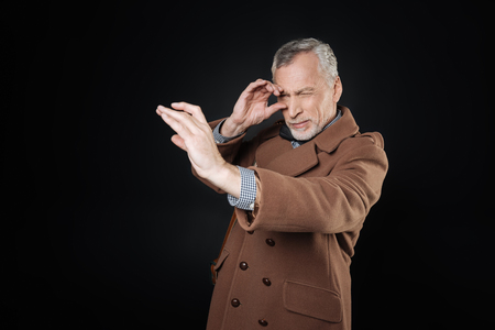 narrowly: Attractive pensioner looking narrowly into fictitious telescope Stock Photo