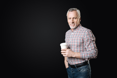 Positive delighted elderly man holding paper cup in left hand
