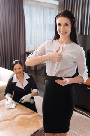 hotel staff: Attractive nice woman showing thumbs up gesture