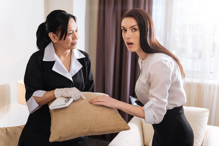 hotel staff: Unhappy surprised woman noticing a spot
