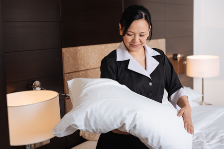 bed sheet: Positive hard working hotel maid looking at the pillow