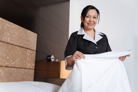 hotel staff: Pleasant positive woman holding a sheet