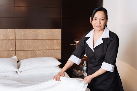 hotel staff: Positive delighted woman standing in the hotel room
