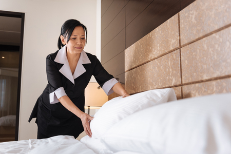 hotel staff: Pleasant delighted hotel maid making the bed Stock Photo