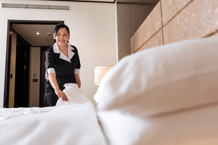 bed sheet: Delighted professional hotel maid being in a positive mood