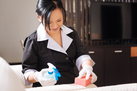 Joyful nice hotel maid doing the room cleaning