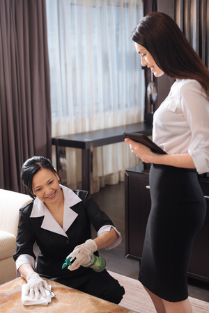 Attractive professional manager looking at the chamber maid