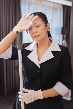 hotel staff: Hard working Asian chambermaid closing her eyes Stock Photo