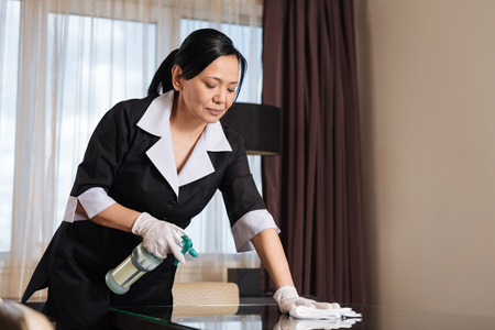 hotel staff: Serious hard working chambermaid making the table clean