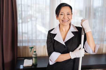 Happy delighted chambermaid holding a mop