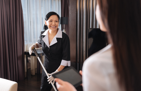 hotel staff: Positive happy chambermaid cleaning the room Stock Photo