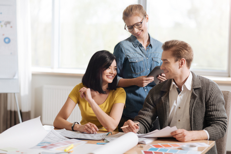 Happy hard working designers talking to each other Stock Photo