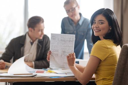 Joyful positive woman holding an engineering drawing Stock Photo