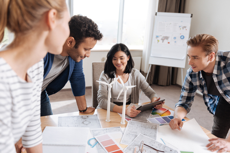 Positive joyful colleagues discussing windmill models Stock Photo