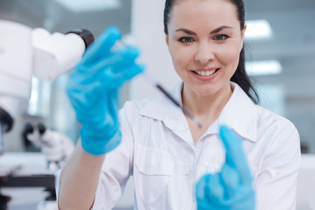medical laboratory: Positive delighted practitioner testing new reagent