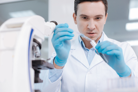 medical laboratory: Portrait of serious scientist pouring down reagent