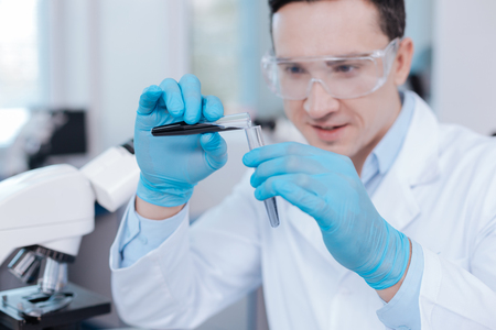 medical laboratory: Portrait of enigmatical practitioner while mixing chemical agents Stock Photo