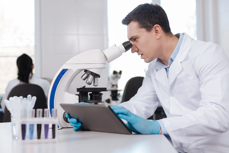 medical laboratory: Confident brunette looking into microscope