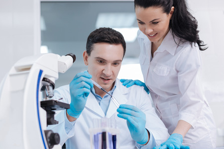 medical laboratory: Attractive competent lab assistant standing near her colleague
