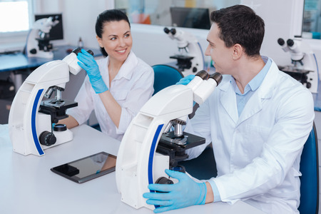 medical laboratory: Pretty smiling researcher sitting opposite her colleague