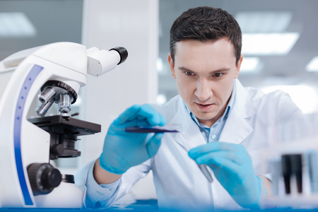 medical laboratory: Handsome medical worker examining chemical agent Stock Photo