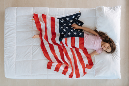 Nice pleasant girl being covered with the US flag Stock Photo
