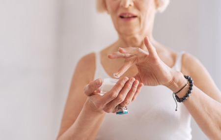 Old female sopping her finger into cream Stock Photo
