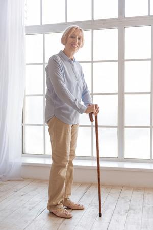 Foto vertical de mujer encantada de pie en posición semi Foto de archivo