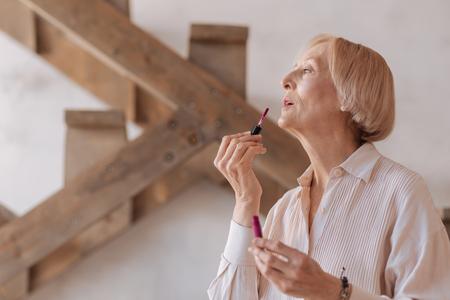 gerontology: Fashionable female putting up her lipstick