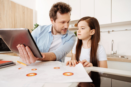 Father showing something on a tablet to his daughter