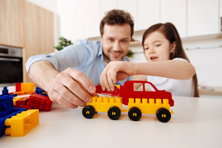 Loving father and his little daughter assembling construction set Imagens